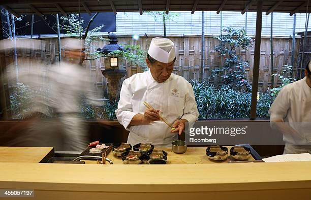 Yoshihiro Murata master chef for Kikunoi Japanese restaurant and chairman of the Japanese Culinary Academy center cooks in the restaurant kitchen...