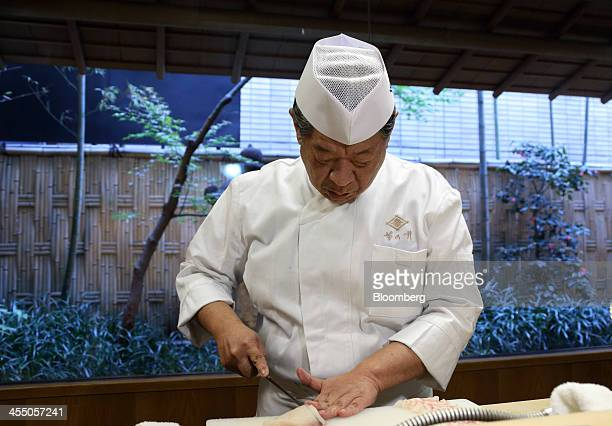 Yoshihiro Murata master chef for Kikunoi Japanese restaurant and chairman of the Japanese Culinary Academy slices a piece of Sashimi in the...