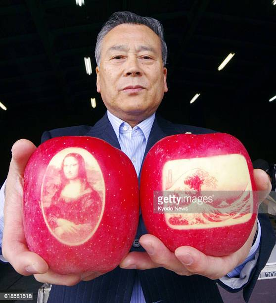 Yoshihiro Sato who runs a company selling agricultural equipment holds apples decorated with images of the Mona Lisa and Thirtysix Views of Mount...