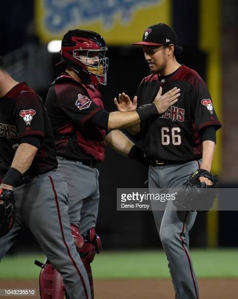 Yoshihisa Hirano of the Arizona Diamondbacks is congratulated by Alex Avila after beating the San Diego Padres 54 in a baseball game at PETCO Park on...