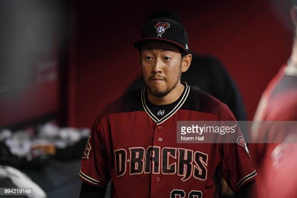 Yoshihisa Hirano of the Arizona Diamondbacks talks with teammates in the dugout after pitching in the tenth inning against the San Diego Padres at...