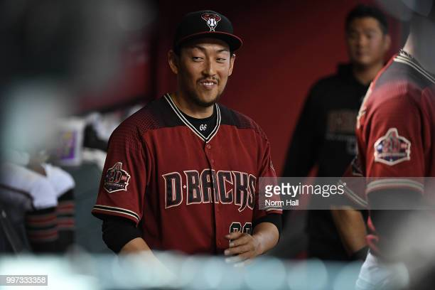 Yoshihisa Hirano of the Arizona Diamondbacks talks with teammates in the dugout after pitching during the tenth inning against the San Diego Padres...