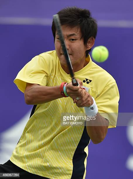 Yoshihito Nishioka of Japan hits a return against Lu YenHsun of Taiwan in their men's singles tennis final match at the Yeorumui Tennis Courts venue...