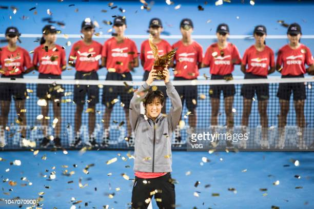 Yoshihito Nishioka of Japan holds the trophy after winning the final match against PierreHugues Herbert of France on day 7 of the ATP Shenzhen Open...