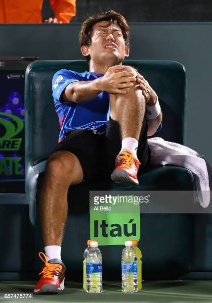 Yoshihito Nishioka of Japan injures his left knee against Jack Sock during day 5 of the Miami Open at Crandon Park Tennis Center on March 24 2017 in...