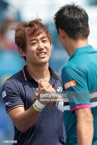 Yoshihito Nishioka of Japan is congratulated by Kei Nishikori of Japan after their match during the Western Southern Open at Lindner Family Tennis...