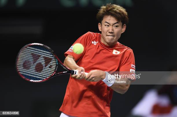 Yoshihito Nishioka of Japan plays a backhand in his match against Gilles Simon of France during the Davis Cup by BNP Paribas first round singles...