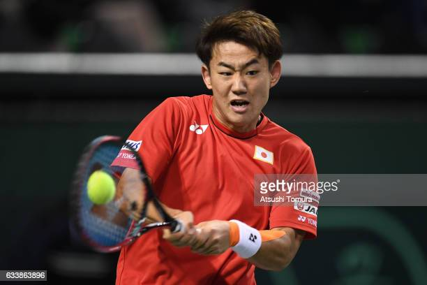 Yoshihito Nishioka of Japan plays a backhand in his match against Nicolas Mahut of France during the Davis Cup by BNP Paribas first round singles...