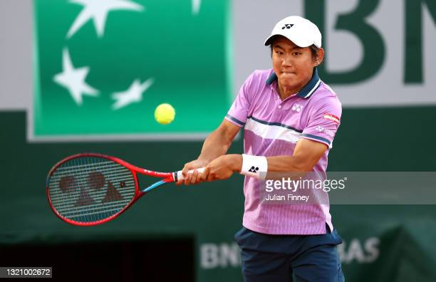 Yoshihito Nishioka of Japan plays a backhand in their mens singles first round match against Jo-Wilfried Tsonga of France on day two of the 2021...