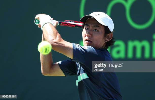 Yoshihito Nishioka of Japan plays a shot against Alex de Minaur of Australia during Day 4 of the Miami Open at the Crandon Park Tennis Center on...