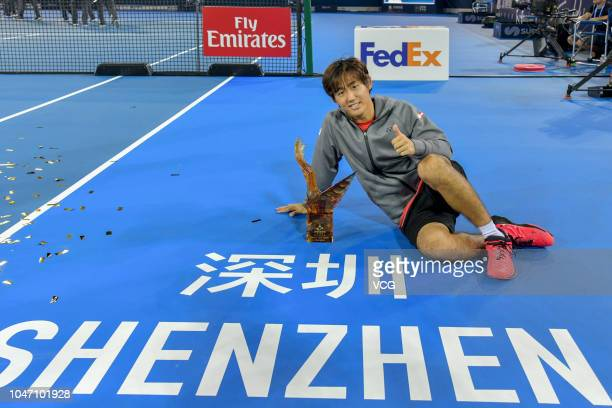 Yoshihito Nishioka of Japan poses with the trophy after winning the final match against PierreHugues Herbert of France on day 7 of the ATP Shenzhen...