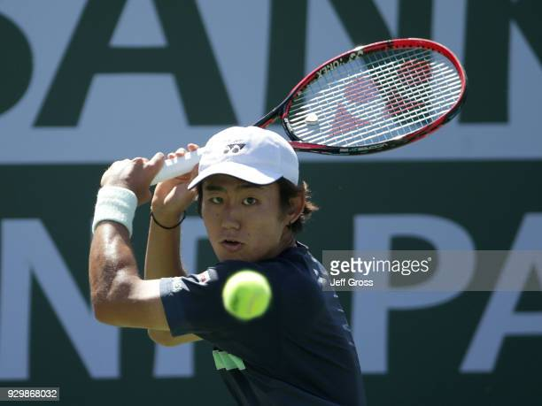 Yoshihito Nishioka of Japan returns a backhand to Marcos Baghdatis of Cyprus during the BNP Paribas Open at the Indian Wells Tennis Garden on March 9...