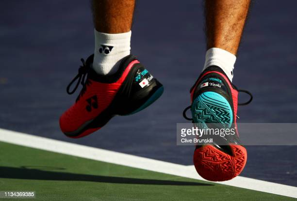 Yoshihito Nishioka of Japan serves against Denis Kudla of the United States during their men's singles first round match on day four of the BNP...