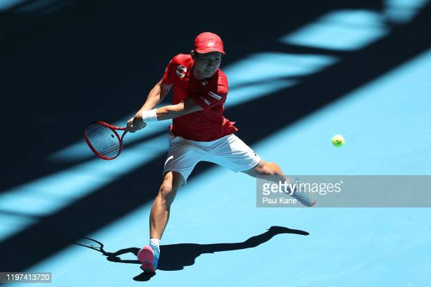 Yoshihito Nishioka of Team Japan plays a backhand to Pablo Cuevas of Team Uruguay during day two of the 2020 ATP Cup Group Stage at RAC Arena on...