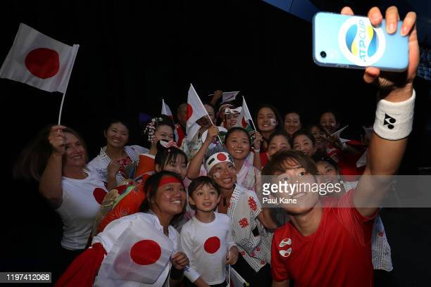 Yoshihito Nishioka of Team Japan takes a selfie with Japanese supporters after winning his singles match against Pablo Cuevas of Team Uruguay during...