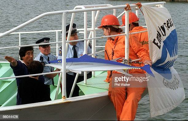 Yoshiji Kikuchi captain of the Japanese Southern Bluefin fishing ship Seiryo Maru No12 motions for Greenpeace protestors Carmen Gravett and Matt...