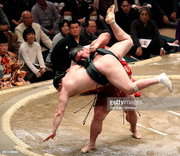 Yoshikaze lifts Mongolian wrestler Chiyoshoma to throw during day one of the Grand Sumo New Year Tournament at Ryogoku Kokugikan on January 8 2017 in...