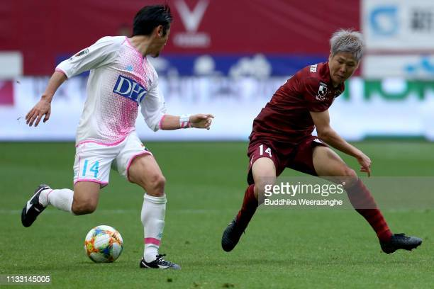 Yoshiki Takahashi of Sagan Tosu and Hirotaka Mita of Vissel Kobe compete for the ball during the JLeague J1 match between Vissel Kobe and Sagan Tosu...