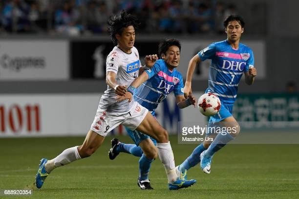 Yoshiki Takahashi of Sagan Tosu and Ken Tokura of Consadole Sapporo compete for the ball during the JLeague J1 match between Sagan Tosu and Consadole...