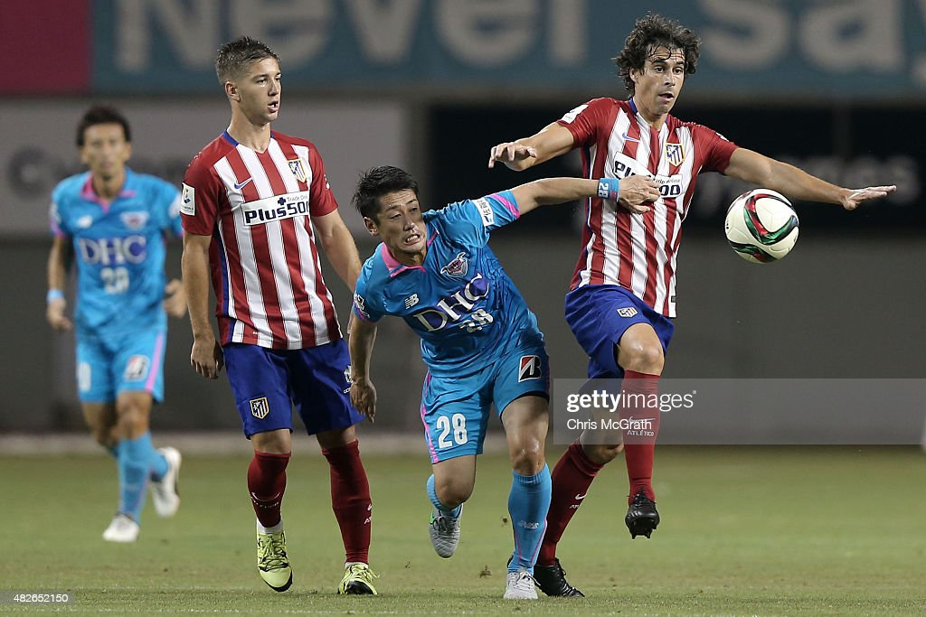 Yoshiki Takahashi #28 of Sagan Tosu contests the ball with Tiago Cardoso #5 of Atletico Madrid during the friendly match between Atletico Madrid and Sagan Tosu F.C. at Tosu Stadium on August 1, 2015 in Tosu, Japan.