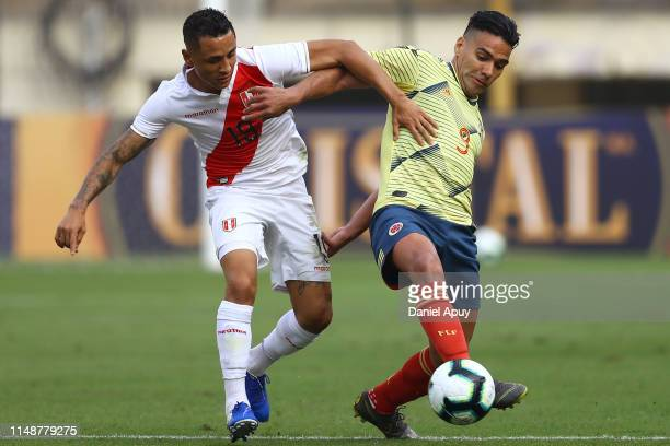 Yoshimar Yotún of Peru and Radamel Falcao of Colombia compete for the ball during a friendly match between Peru and Colombia at Estadio Monumental on...
