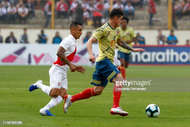 Yoshimar Yotun of Peru fights for the ball with James Rodriguez of Colombia during a friendly match between Peru and Colombia at Estadio Monumental...
