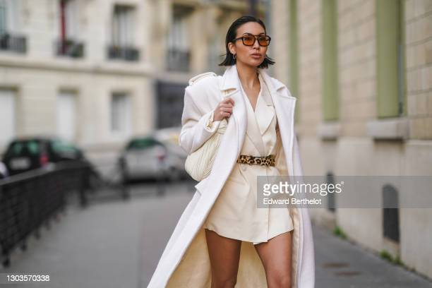 Yoshino Mia wears brown clear sunglasses from Vehla eyewear, a white long trench wool coat designed by herself, a white oversized long blazer double...