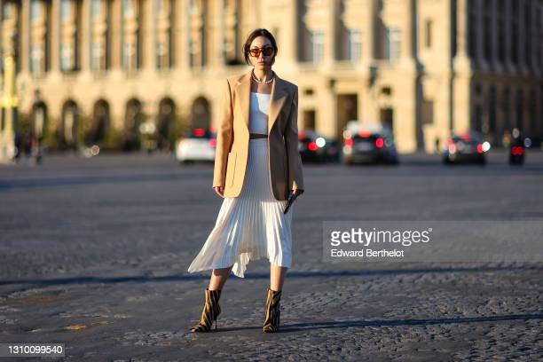 Yoshino Mia wears sunglasses from Vehla Eyewear, a pearl necklace from Amber Sceats, a beige oversized blazer jacket from Barbara Bui, a white...