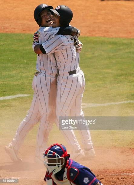 Yoshinobu Takahashi and Kazuhiro Wada of Japan celebrate after Takahashi scored the winning run on a sacrifice fly hit by Michihiro Ogasawarea to...