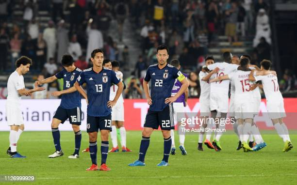 Yoshinori Muto and Maya Yoshida of Japan show dejection while Qatari players celebrate during the Asian Cup final match between Japan and Qatar at...