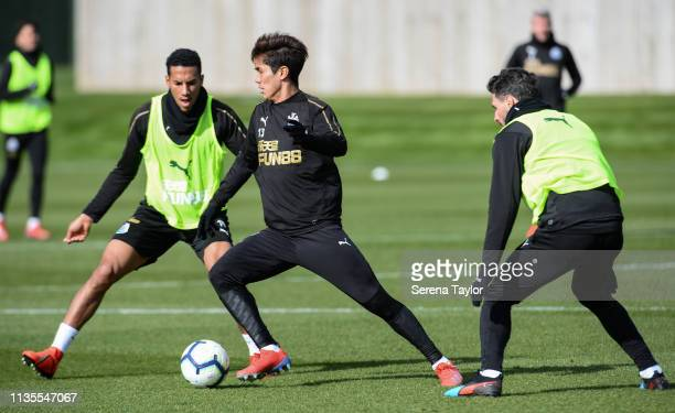 Yoshinori Muto controls the ball whilst being pursued by Isaac Hayden and Fabian Schar during the Newcastle United Training Session at the Newcastle...