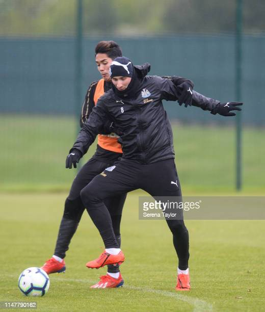 Yoshinori Muto holds on to Jonjo Shelvey as they jostle for the ball during the Newcastle United Training session at the Newcastle United Training...