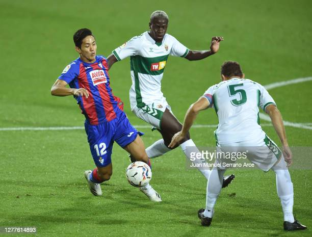 Yoshinori Muto of Eibar is challenged by Omenuke Mfulu of Elche during the La Liga Santander match between SD Eibar and Elche CF at Estadio Municipal...