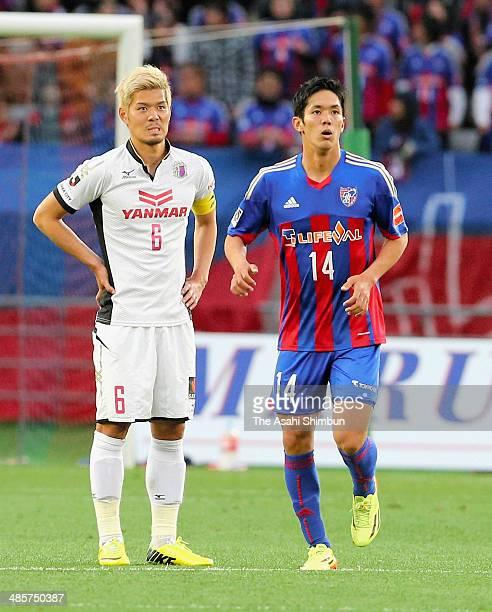 Yoshinori Muto of F.C. Tokyo celebrates scoring his team's second goal while Hotaru Yamaguchi of Cerezo Osaka shows his frustration during the...