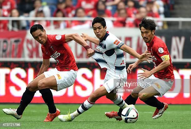 Yoshinori Muto of FC Tokyo competes against Tomoaki Makino and Yuki Abe of Urawa Reds during the JLeague match between Urawa Red Diamonds and FC...