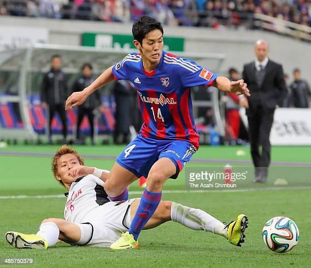 Yoshinori Muto of F.C. Tokyo is tackled by Yoichiro Kakitani of Cerezo Osaka during the J.League match between F.C. Tokyo and Cerezo Osaka at...