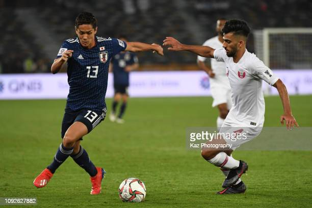 Yoshinori Muto of Japan and Salman Tarek of Qatar compete for the ball during the AFC Asian Cup final match between Japan and Qatar at Zayed Sports...