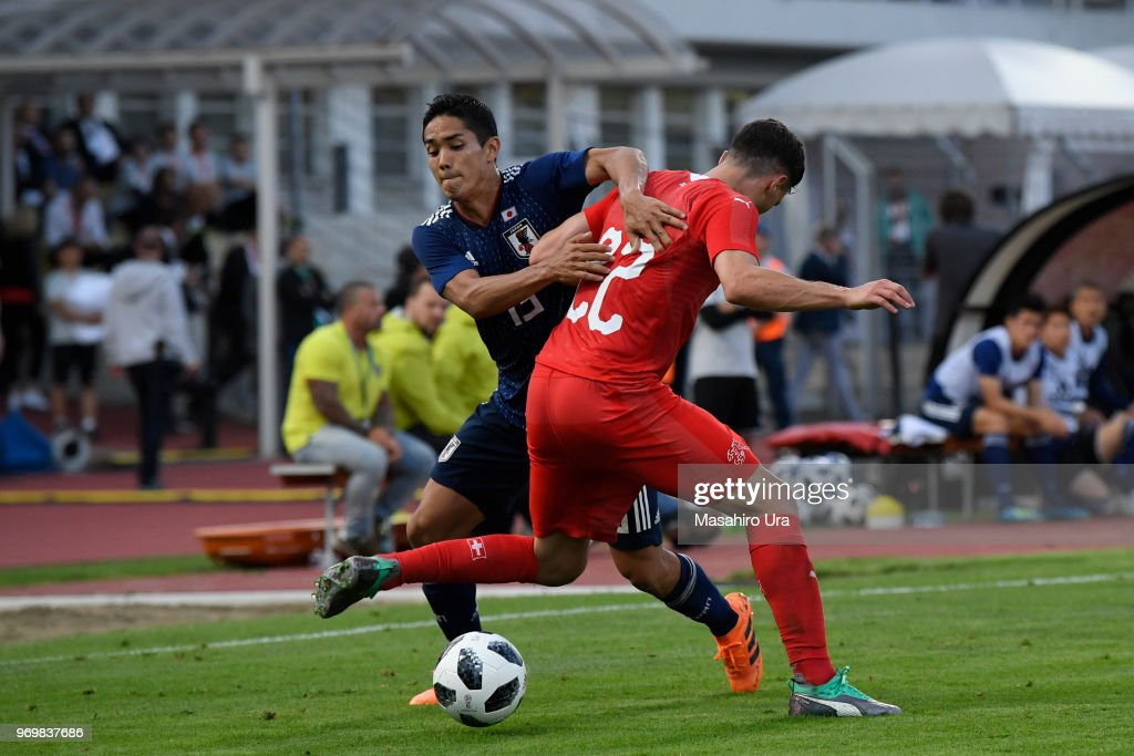 Yoshinori Muto of Japan (L) and Schaer Fabian of Switzerland (R) compete for the ball during the international friendly match between Switzerland and Japan at the Stadium Cornaredo on June 8, 2018 in Lugano, Switzerland.