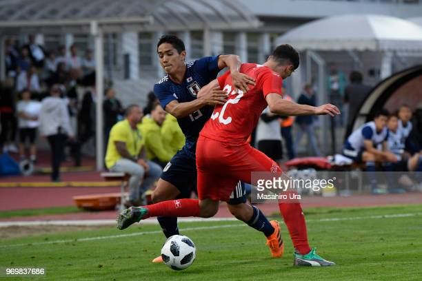Yoshinori Muto of Japan and Schaer Fabian of Switzerland compete for the ball during the international friendly match between Switzerland and Japan...