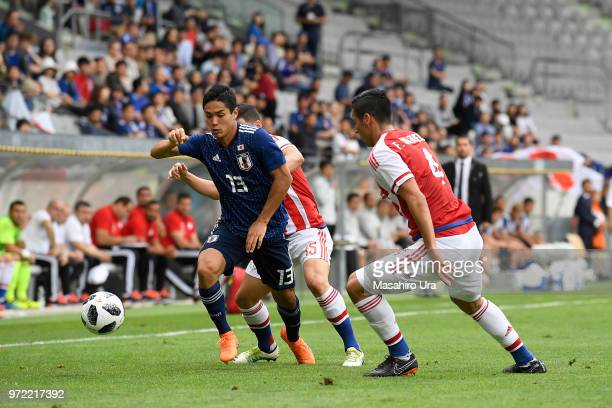 Yoshinori Muto of Japan controls the ball under pressure of Richard Sanchez and Fabian Balbuena of Paraguay during the international friendly match...