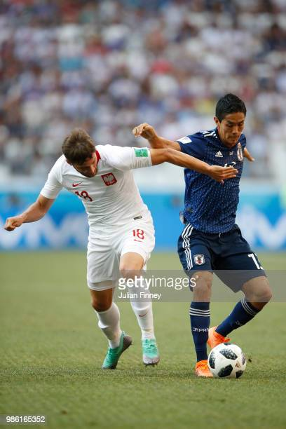 Yoshinori Muto of Japan is challenged by Bartosz Bereszynski of Poland during the 2018 FIFA World Cup Russia group H match between Japan and Poland...