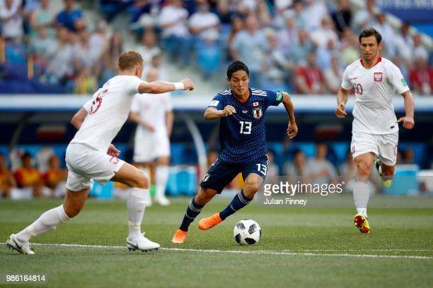 Yoshinori Muto of Japan is challenged by Kamil Glik of Poland during the 2018 FIFA World Cup Russia group H match between Japan and Poland at...