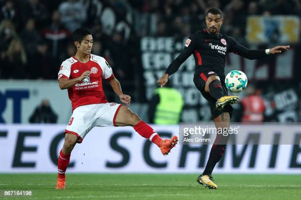 Yoshinori Muto of Mainz and KevinPrince Boateng of Frankfurt battle for the ball during the Bundesliga match between 1 FSV Mainz 05 and Eintracht...