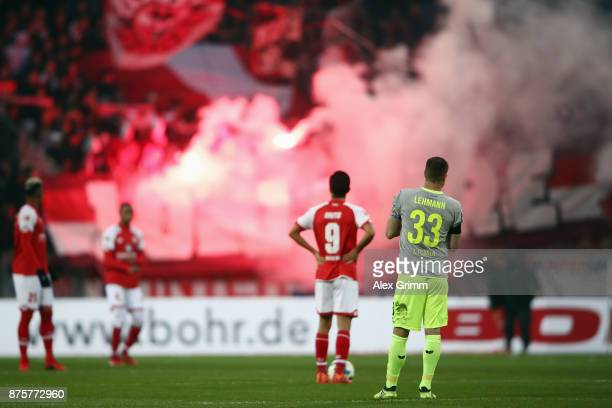 Yoshinori Muto of Mainz and Matthias Lehmann of Koeln react as fans of Koeln burn flares during the Bundesliga match between 1 FSV Mainz 05 and 1 FC...