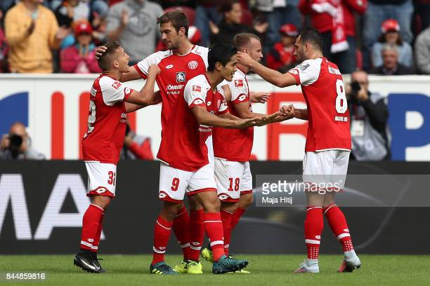 Yoshinori Muto of Mainz celebrates with fellow players after he scored his teams first goal to make it 11 during the Bundesliga match between 1 FSV...
