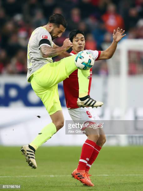 Yoshinori Muto of Mainz is challenged by Dominic Maroh of Koeln during the Bundesliga match between 1 FSV Mainz 05 and 1 FC Koeln at Opel Arena on...