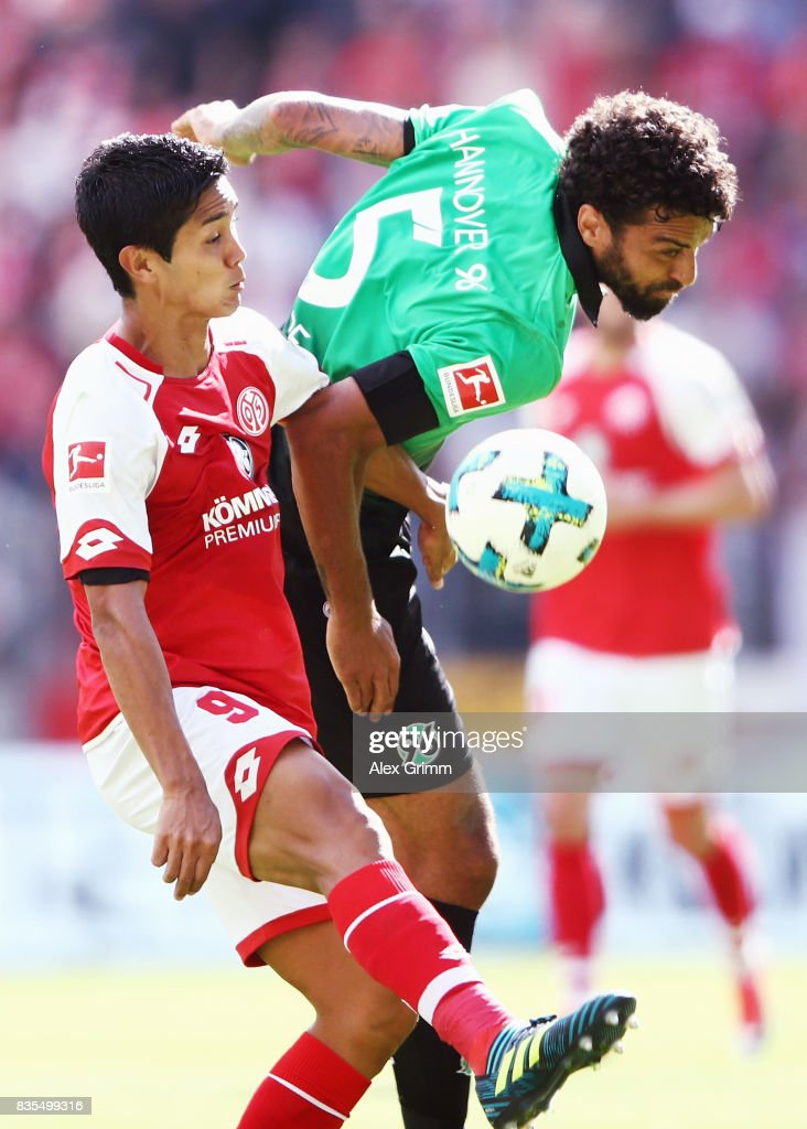 Yoshinori Muto of Mainz is challenged by Felipe of Hannover during the Bundesliga match between 1. FSV Mainz 05 and Hannover 96 at Opel Arena on August 19, 2017 in Mainz, Germany.