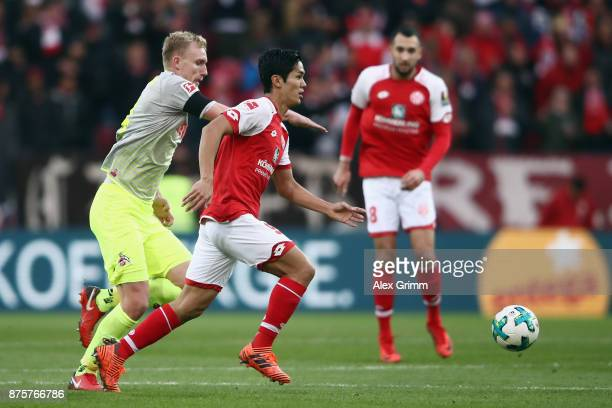 Yoshinori Muto of Mainz is challenged by Frederik Soerensen of Koeln during the Bundesliga match between 1 FSV Mainz 05 and 1 FC Koeln at Opel Arena...