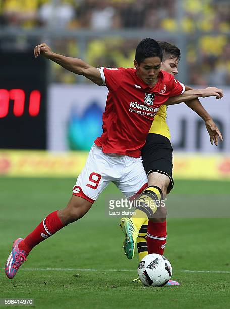 Yoshinori Muto of Mainz is challenged by Julian Weigl of Dortmund during the Bundesliga match between Borussia Dortmund and 1 FSV Mainz 05 at Signal...