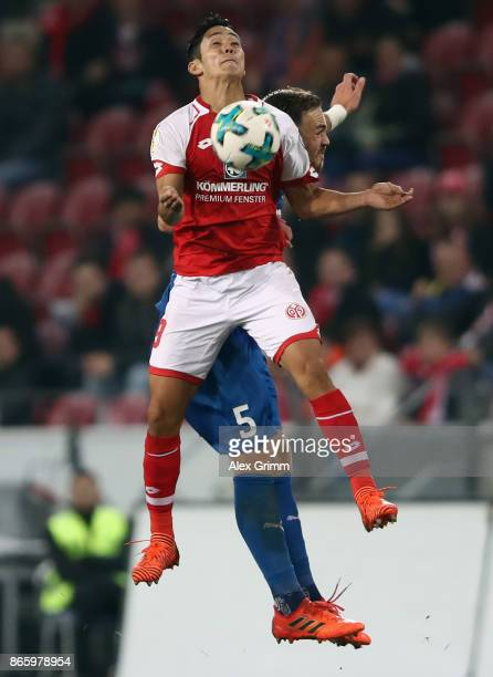 Yoshinori Muto of Mainz is challenged by Rafael Czichos of Kiel during the DFB Cup match between 1 FSV Mainz 05 and Holstein Kiel at Opel Arena on...